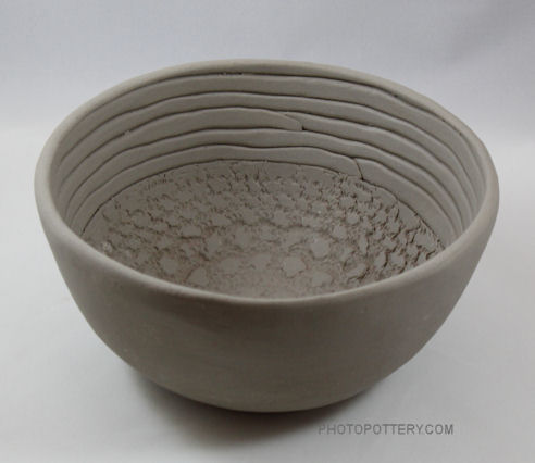 Hand-built serving bowl made on classic mid-size plaster hump mold with textured clay slabs and coils in white stoneware. Clay is in the greenware state